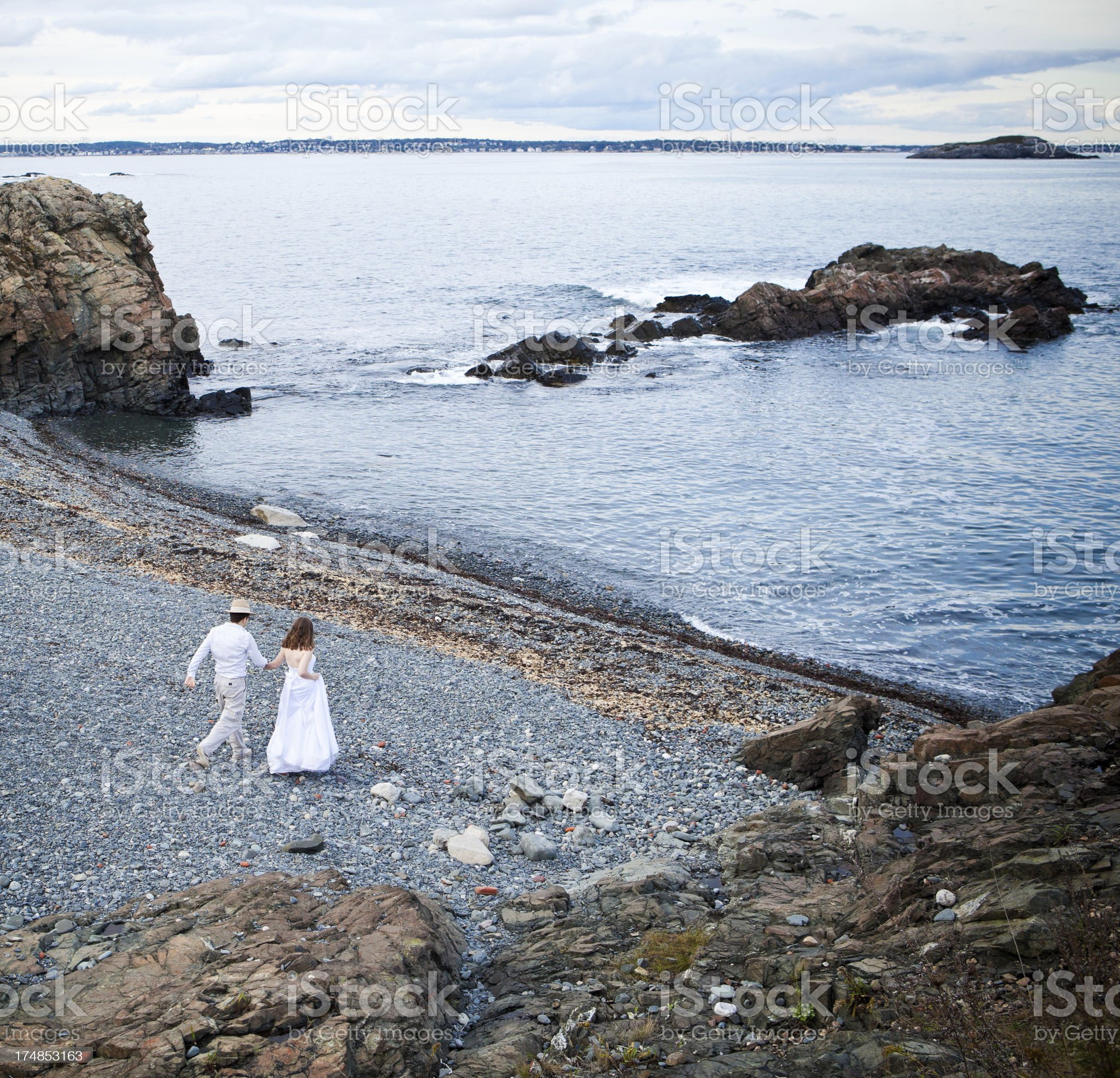 Wedding couple walking to the waterfront royalty-free stock photo