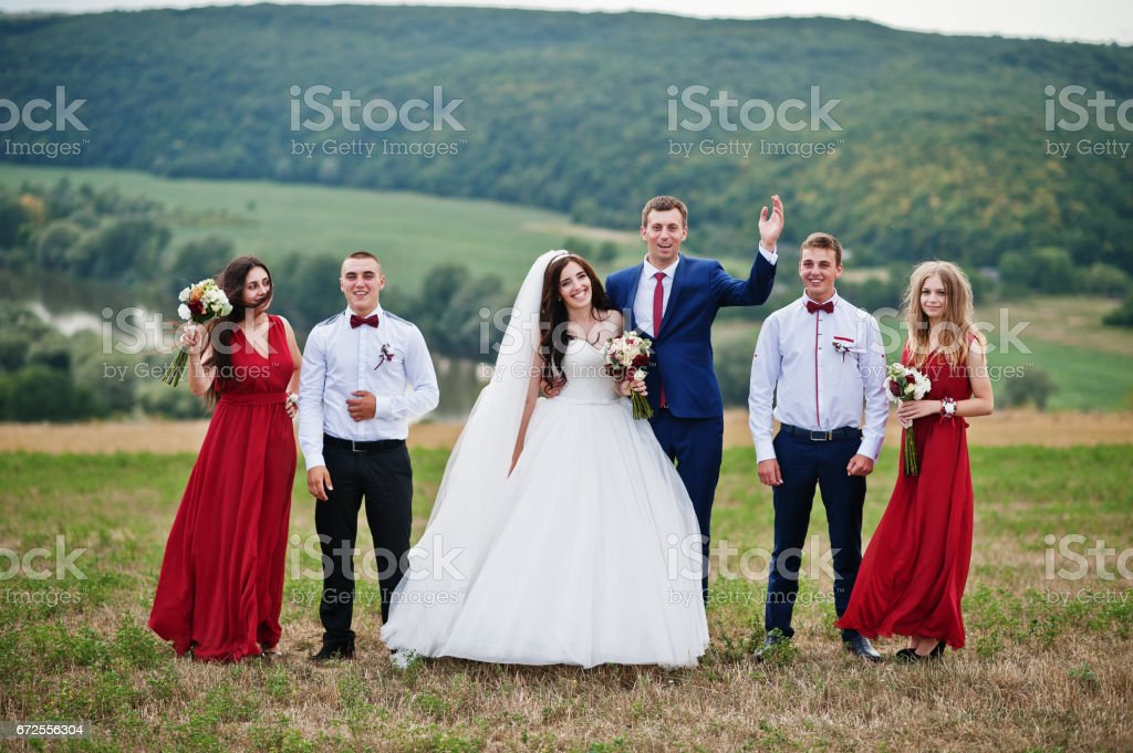 Wedding couple with bridesmaids and best mans walking outdoor. stock photo