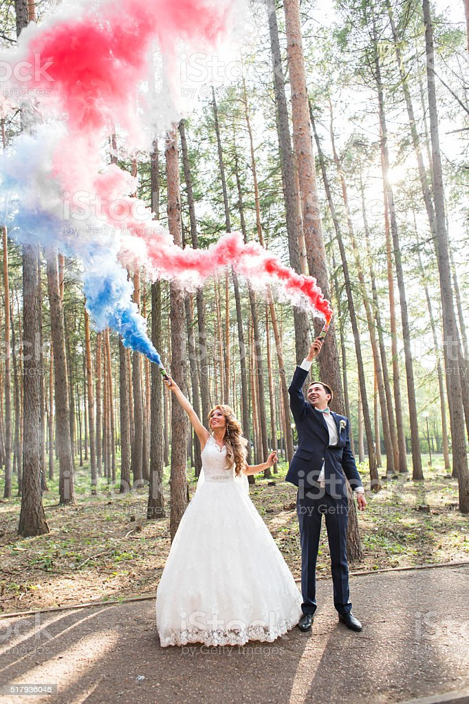 Wedding couple with color smoke in the summer park. Colour stock photo