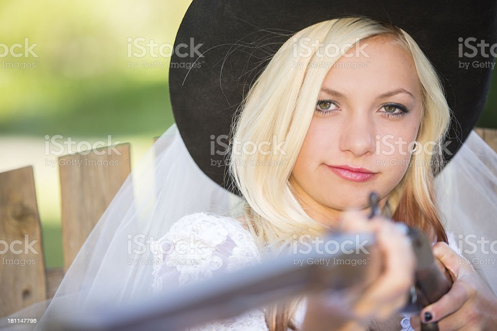 Wedding: Cowboy wedding day, bride in hat holding antique rifle. royalty-free stock photo