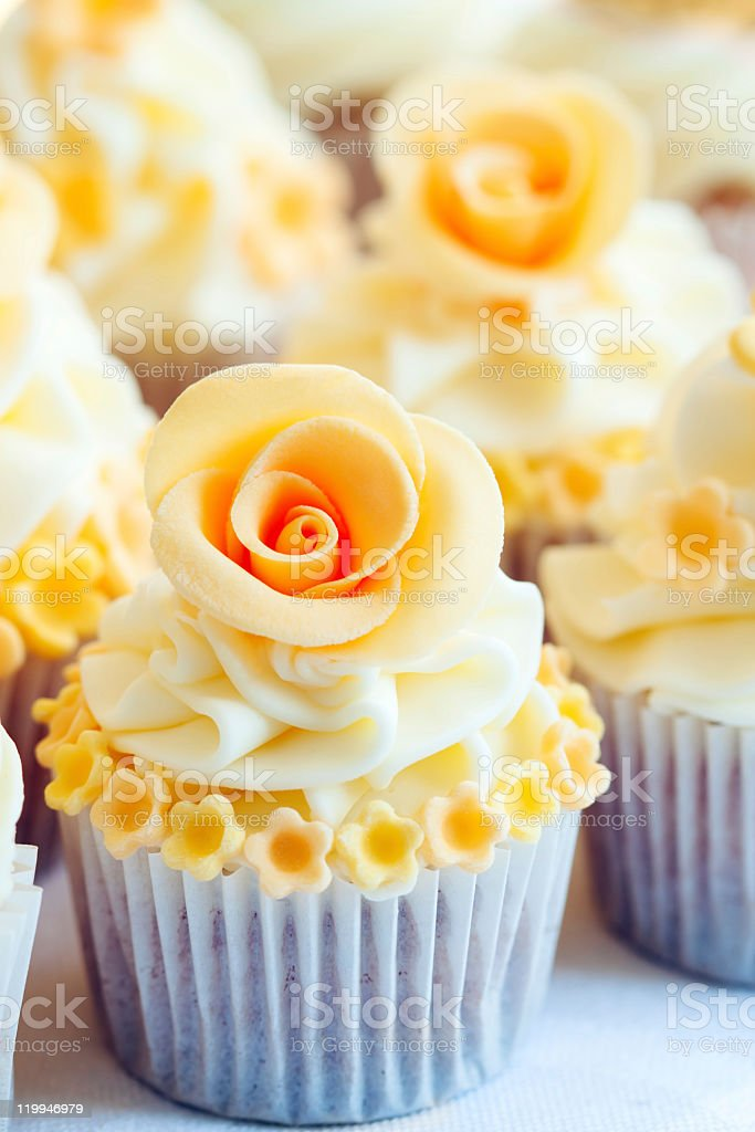 Wedding cupcakes with yellow flowers around and rose on top royalty-free stock photo