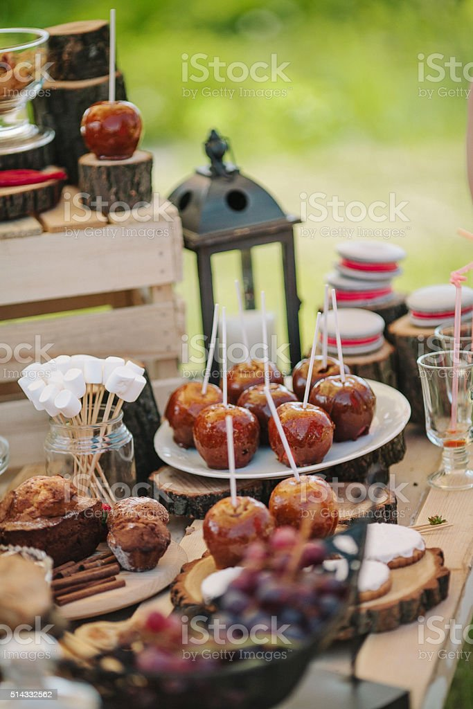 Wedding decor with candles, caramel apples, macaroons, marshmallows stock photo