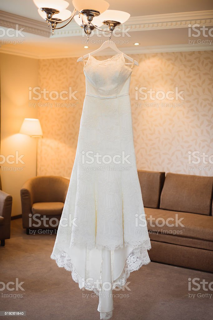 wedding dress hanging on luster at room stock photo