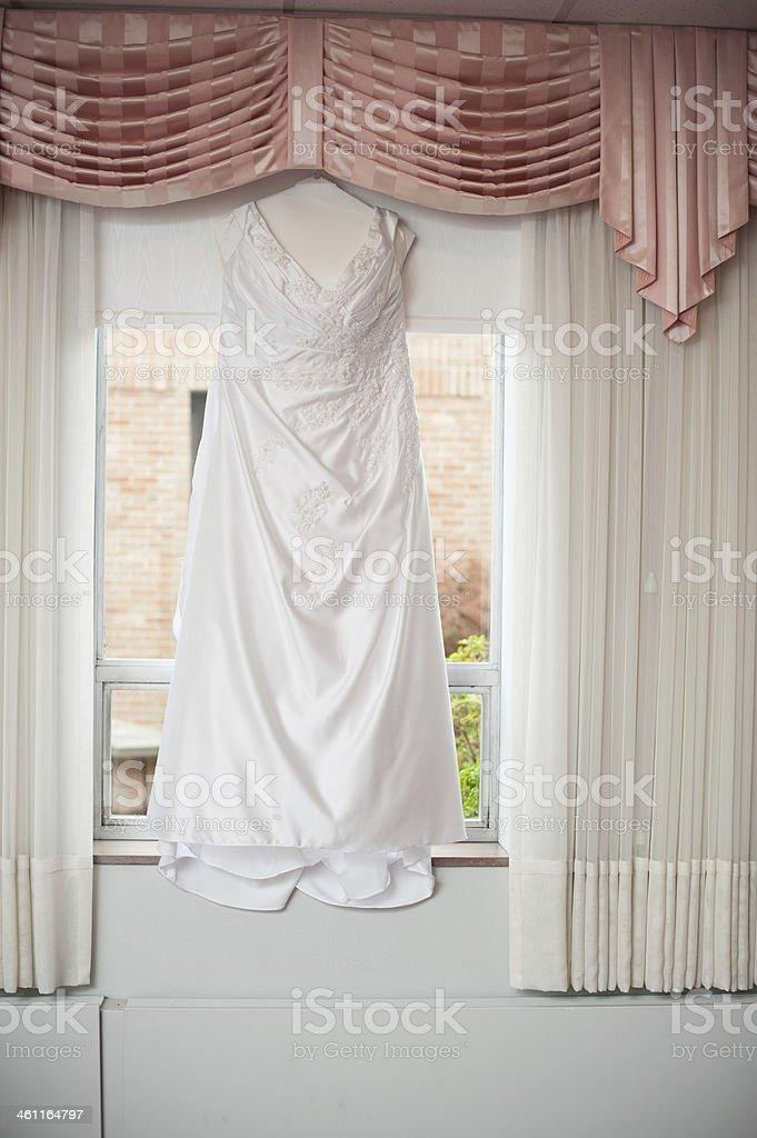 Wedding Dress Hanging Up in Window stock photo
