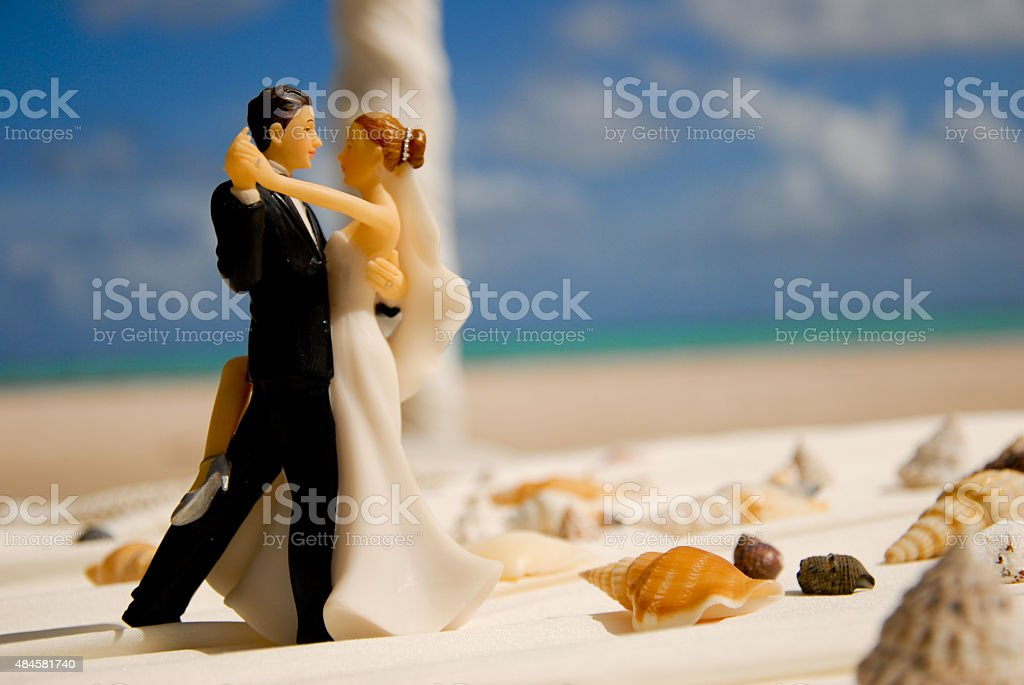 Wedding figurine of bride and groom on the beach stock photo