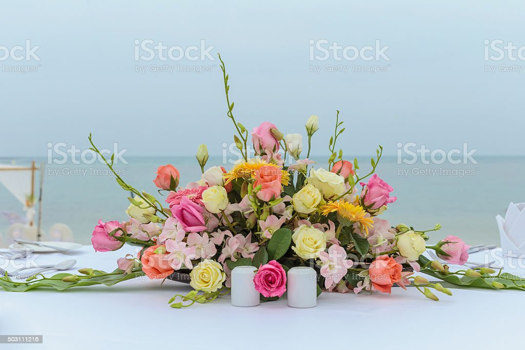 wedding flower setting on the beach stock photo