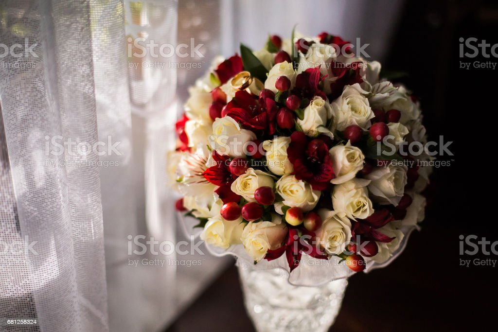 wedding flowers, bouquet of white roses dairy and red flowers, preparing for the wedding, the groom's fees bride morning stock photo