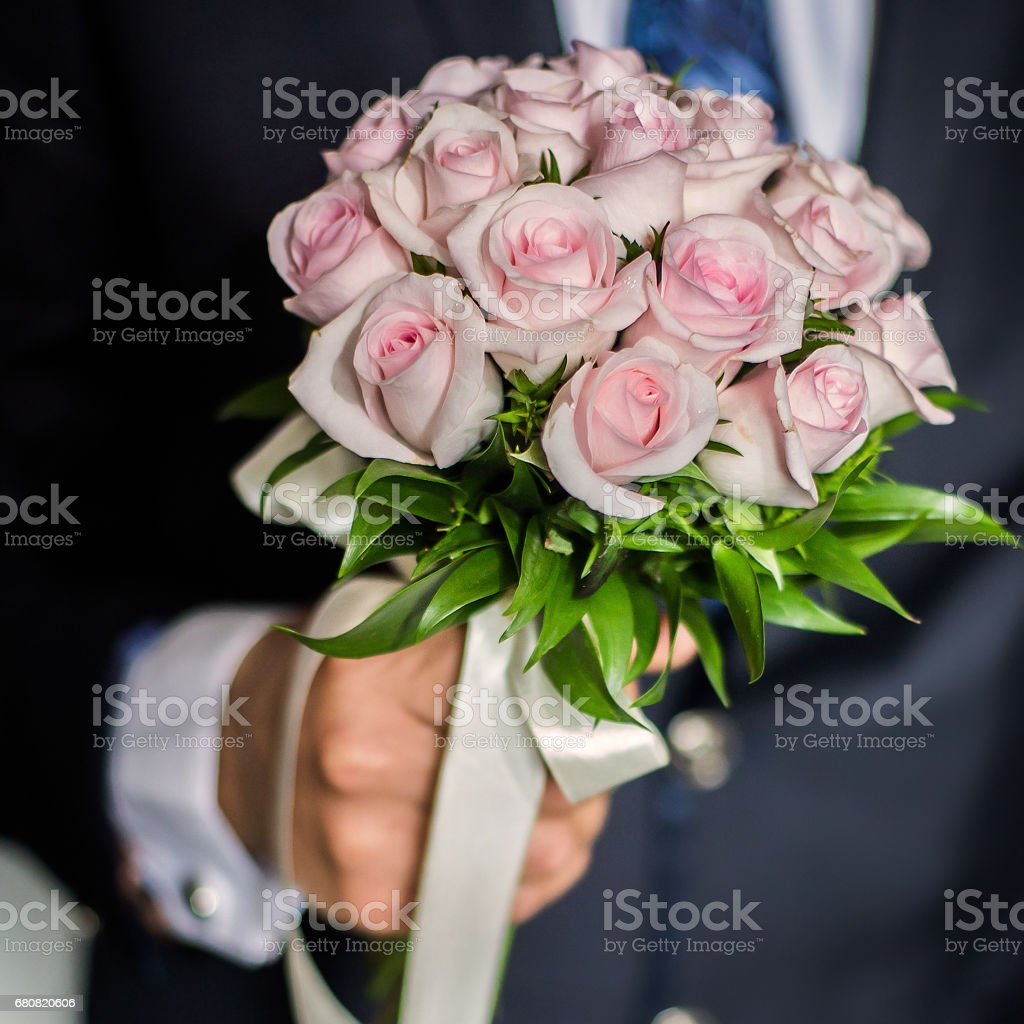 wedding flowers, groom holds bouquet of pink roses, bouquet of roses, bridal bouquet, groom's fees stock photo