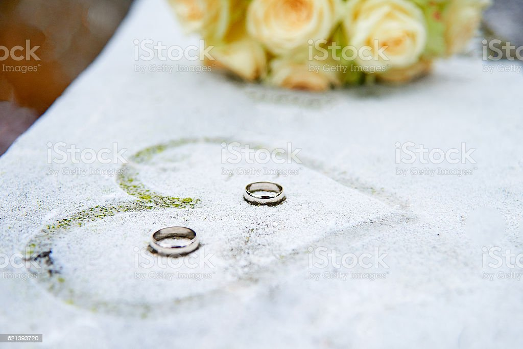 Wedding flowers, rings and painted heart on frozen surface stock photo