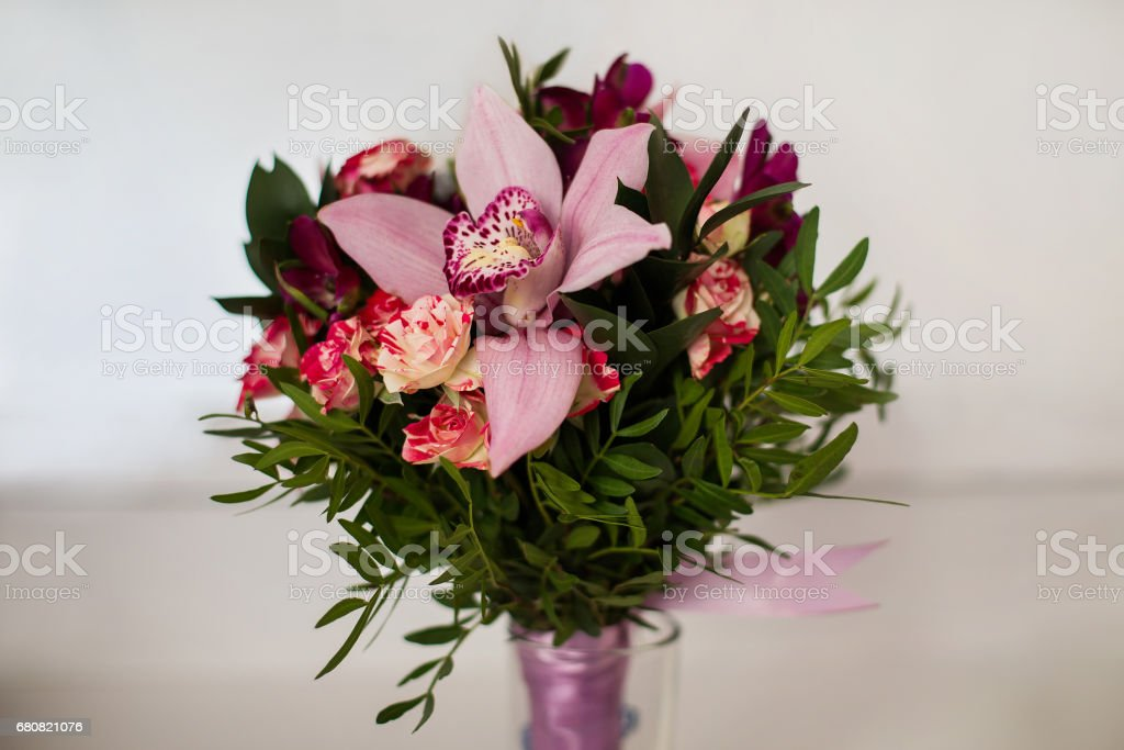 wedding flowers, wedding bouquet of red and pink peach yellow roses and blue violet purple orchid bouquet of blue, purple, purple flowers, roses, orchids, preparing for the wedding, wedding decorations stock photo