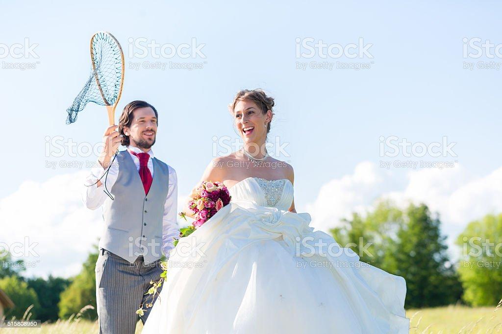 Wedding groom catching bride with net stock photo