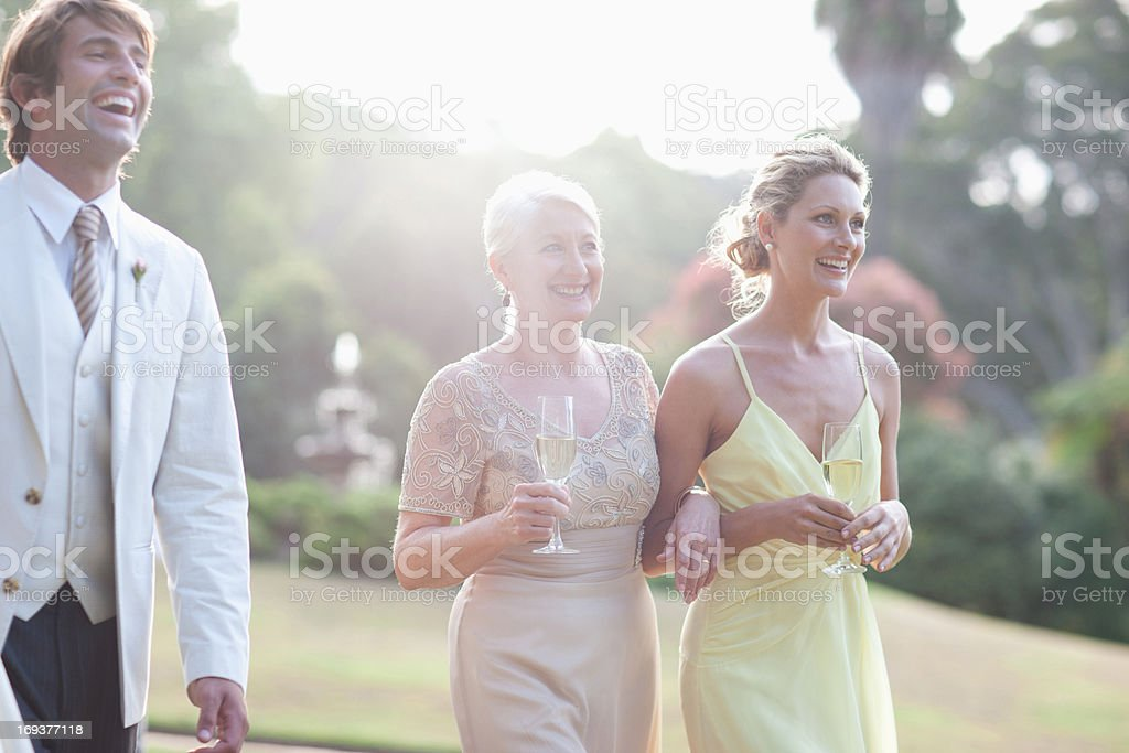 Wedding guests walking across lawn stock photo