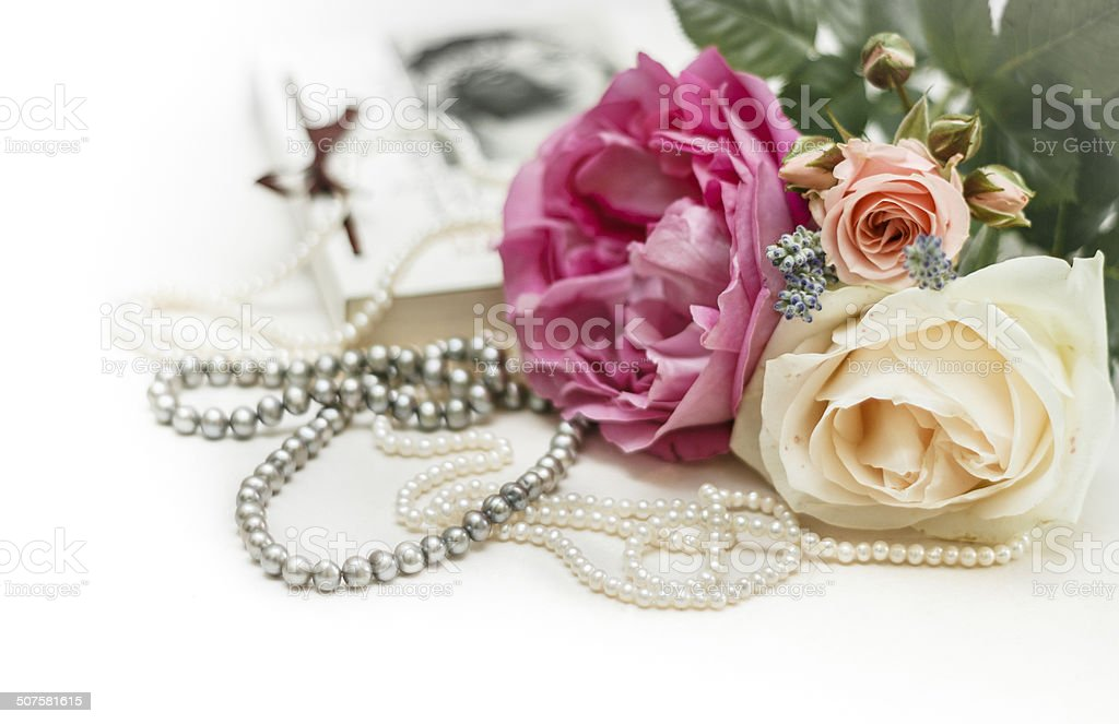 Wedding invitation. Roses with vintage book and pearl necklaces. stock photo