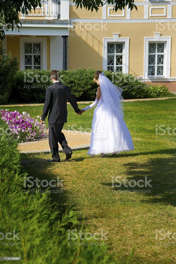 Wedding pair runs on a grass royalty-free stock photo