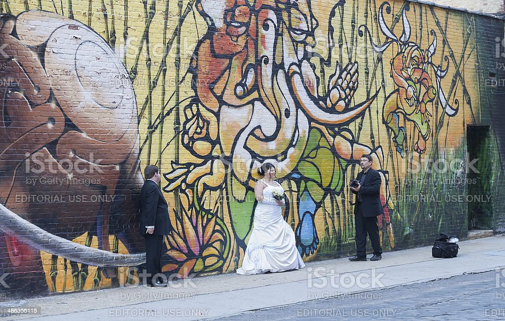 Wedding Photographer & Clients in front of Graffiti Wall. stock photo