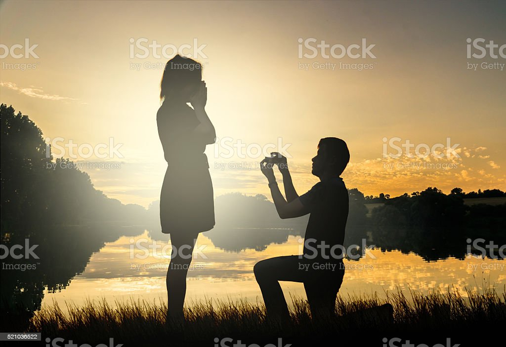 Wedding proposal. Dating at sun set. Man giving ring. stock photo