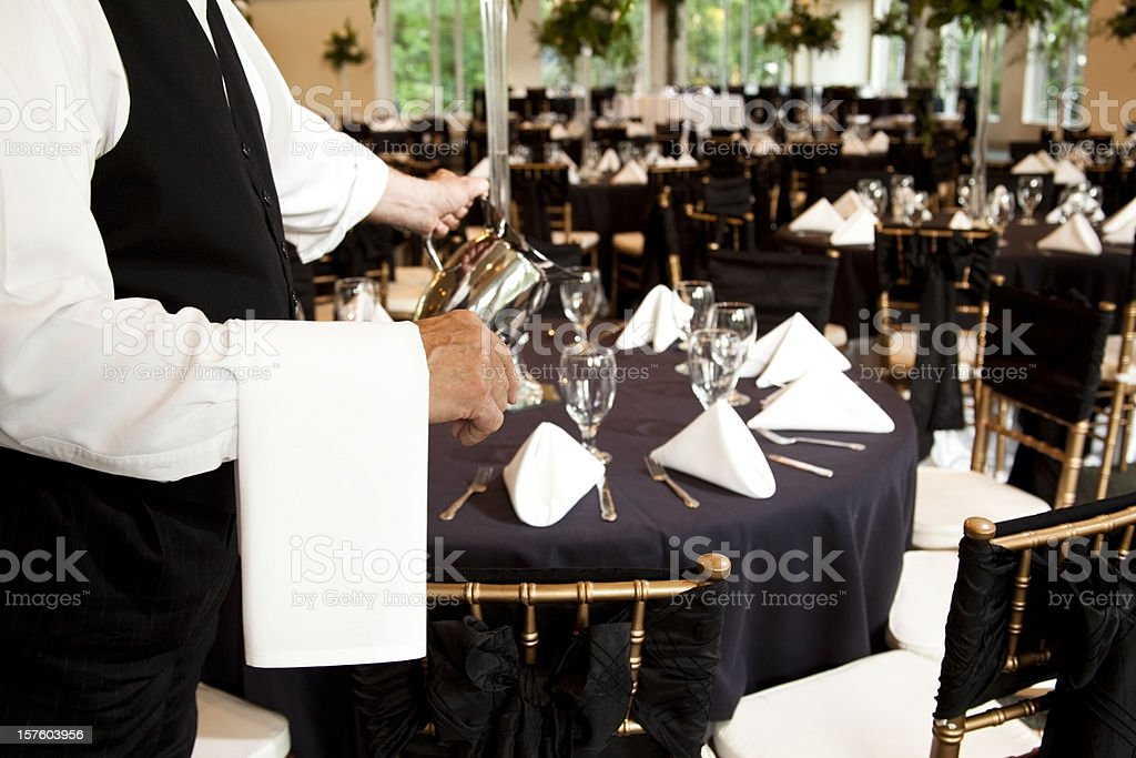 Wedding reception waiter pouring water into glasses. Waitstaff.  Serving. stock photo