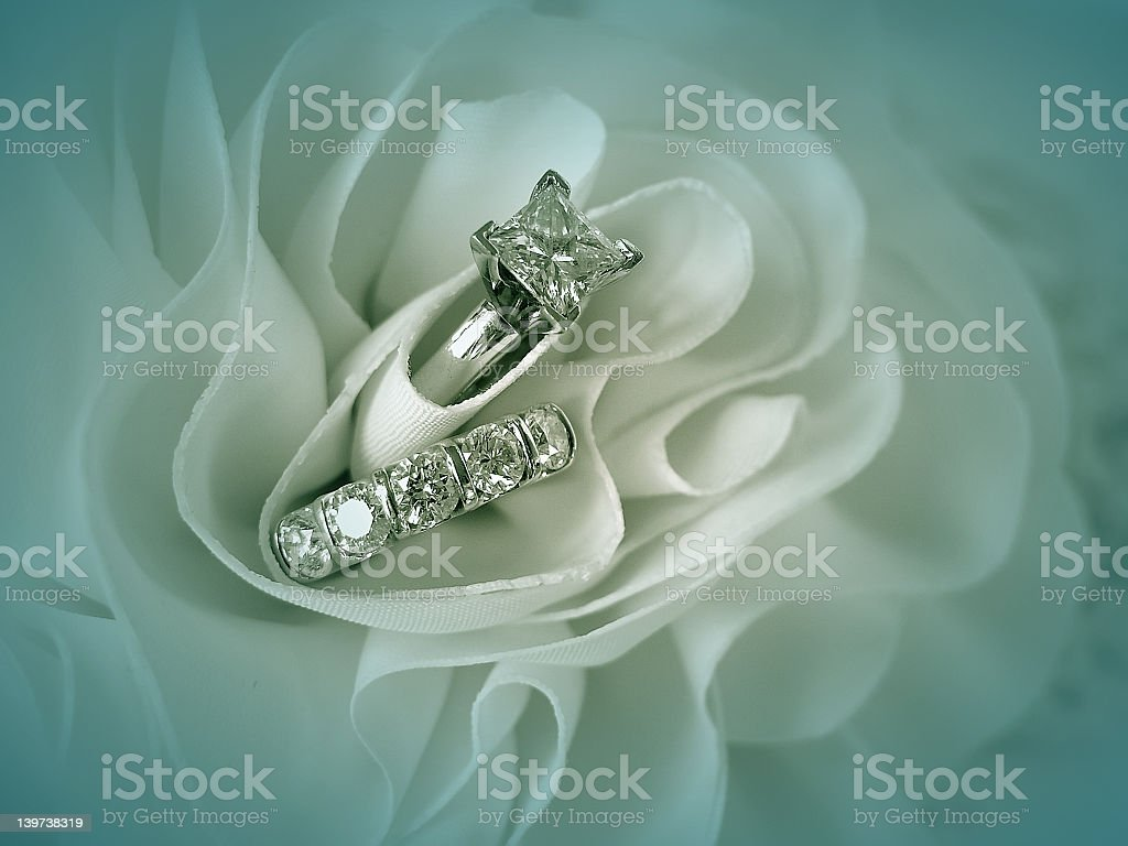 A wedding ring and band in a white fabric royalty-free stock photo