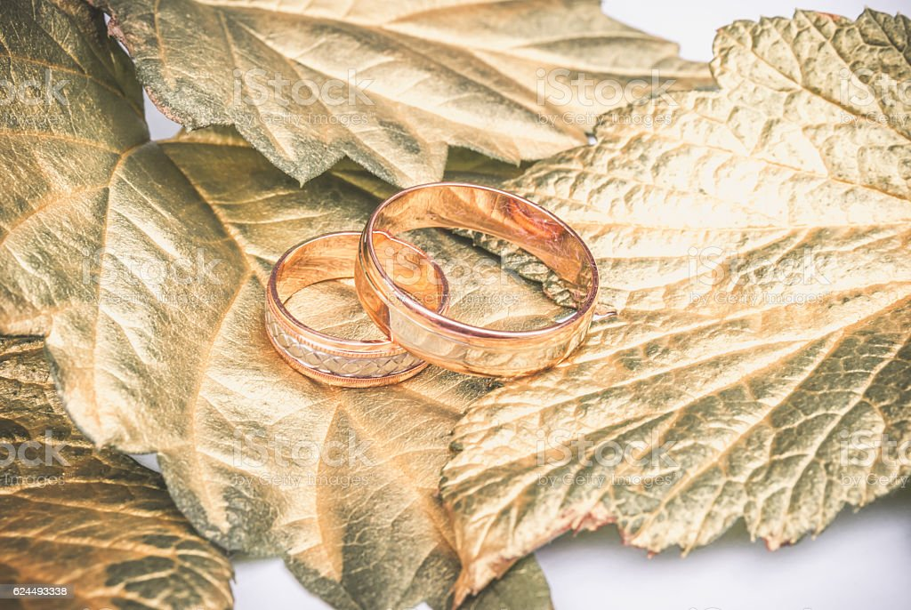 Wedding ring and gold leaves stock photo