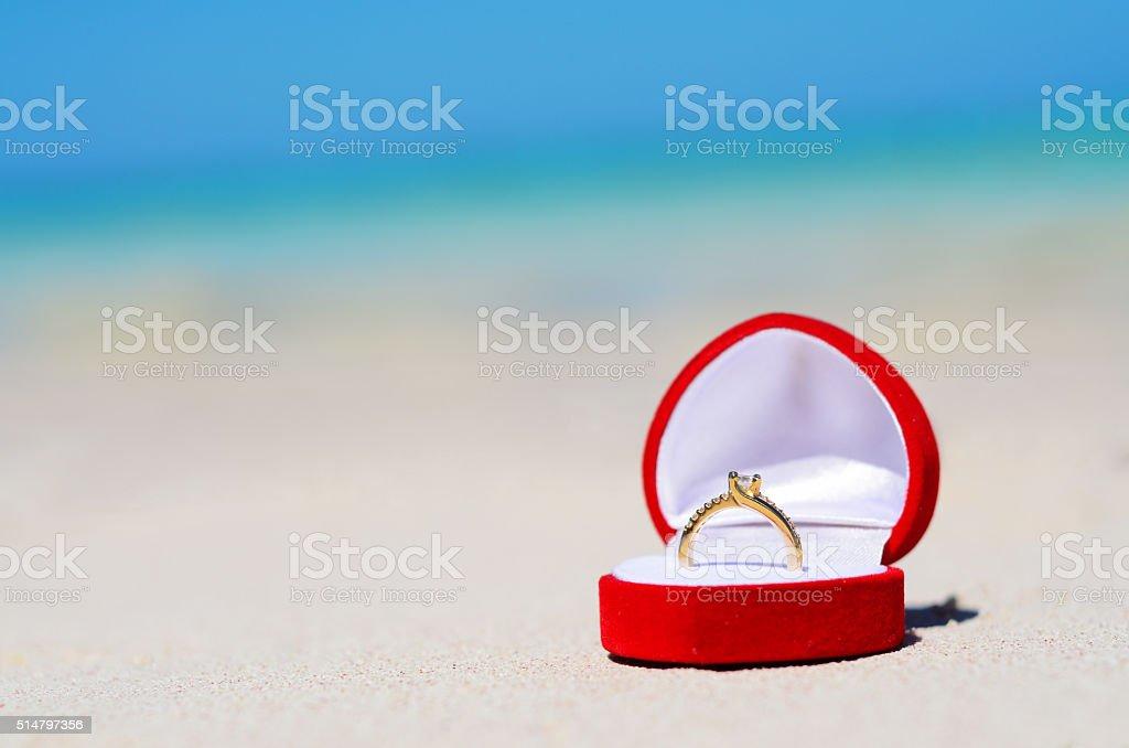 Wedding ring in box on the sandy beach stock photo