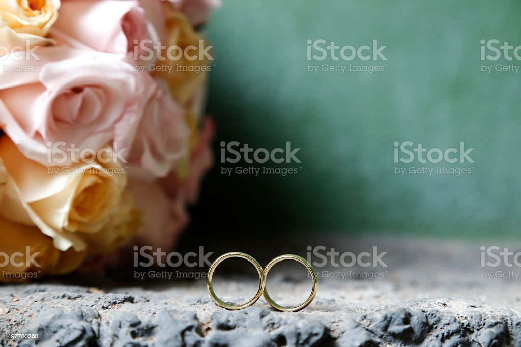 Wedding rings and bouquet of flowers stock photo