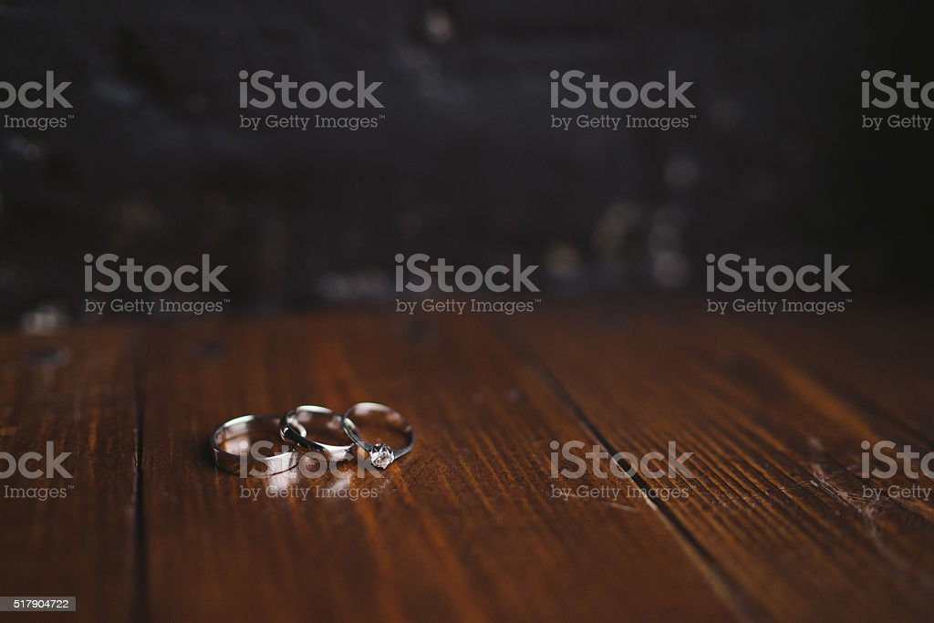 Wedding rings and engagement ring on dark wooden background stock photo