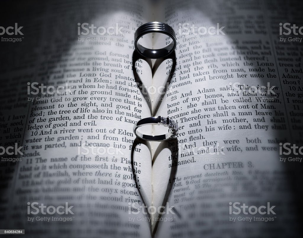 Wedding rings and heart shaped shadow over Bible stock photo