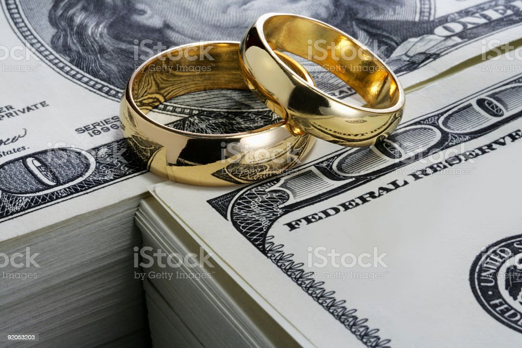 Wedding rings and stack of money stock photo