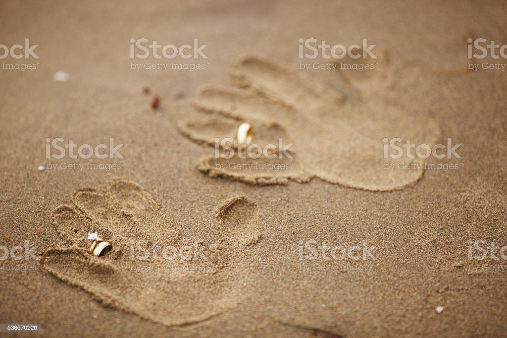 Wedding rings handprints on beach stock photo