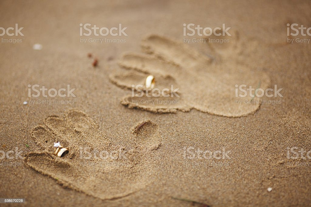 Wedding rings handprints on beach stock photo