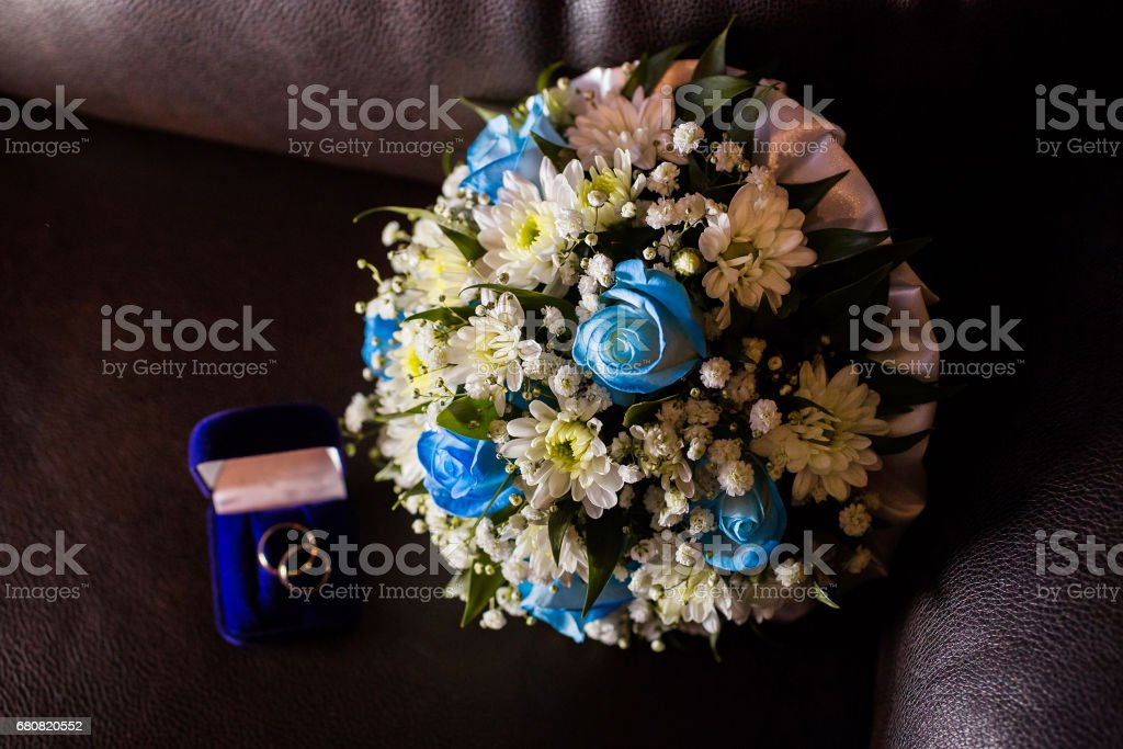 Wedding rings in a blue box, a bridal bouquet of white flowers and blue roses on a blue background temnof, preparing for the wedding stock photo