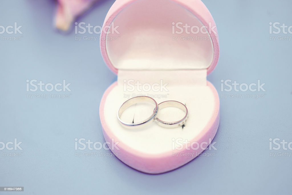 wedding rings in a pink box stock photo