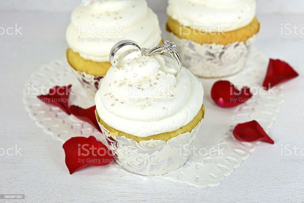 wedding rings in cupcake icing stock photo
