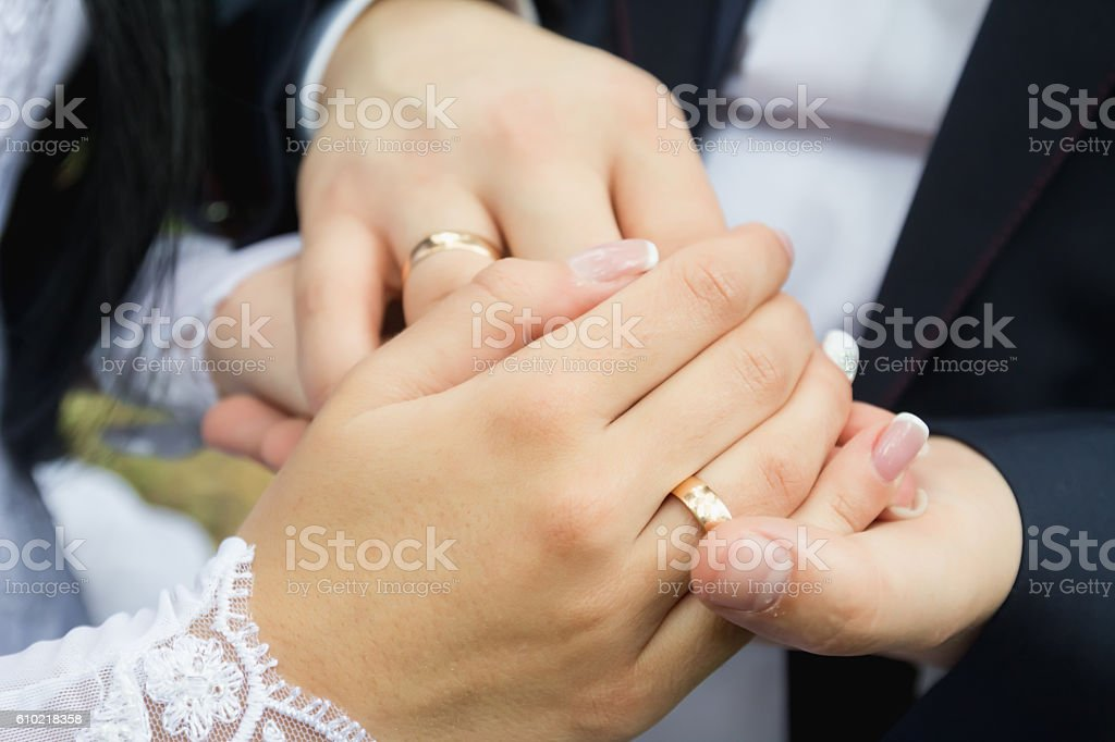 Wedding rings in the hands of men and women stock photo