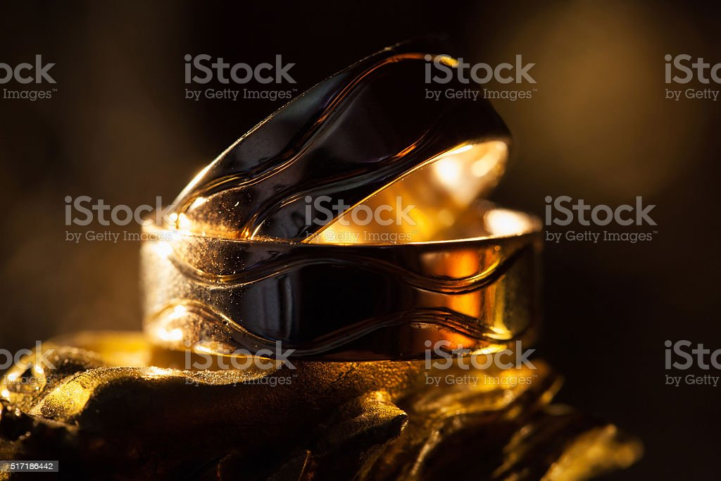 Wedding rings in the rays of yellow light stock photo