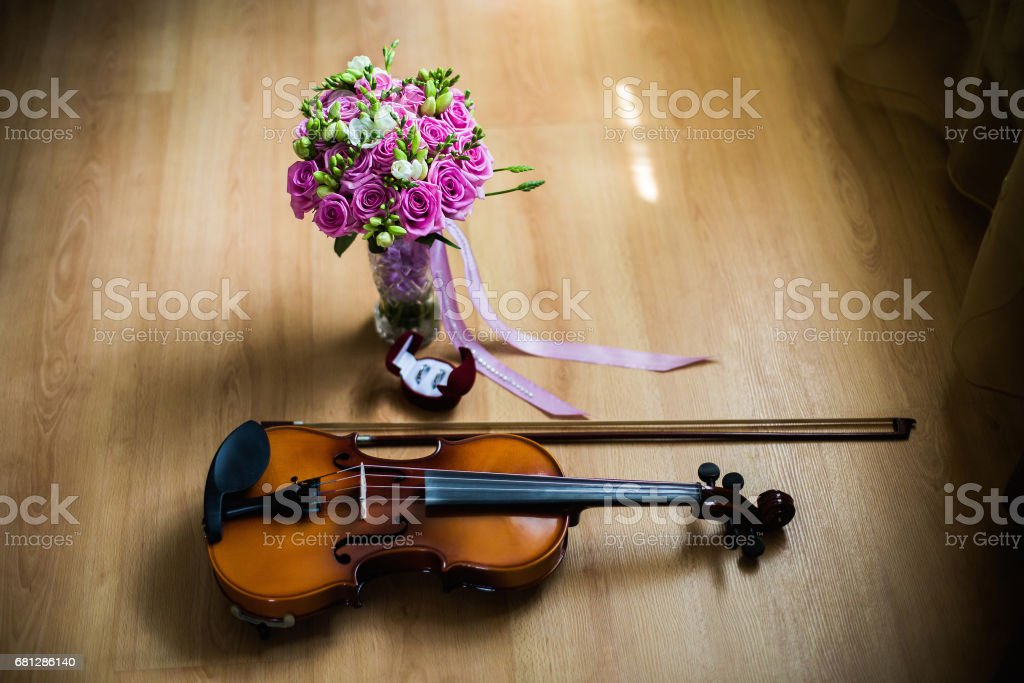 Wedding rings in the red box, a violin and bow, wedding flowers, wedding bouquet of beautiful pink roses and white flowers, rose bouquet, wedding preparation, wedding jewelry stock photo