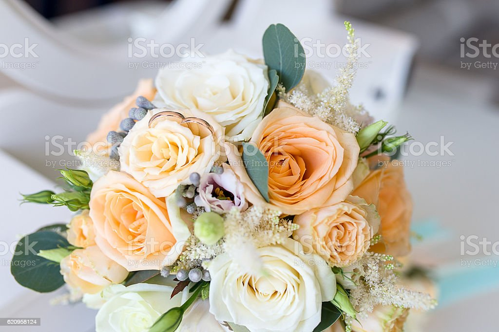 Wedding rings lie on the Bridal bouquet stock photo