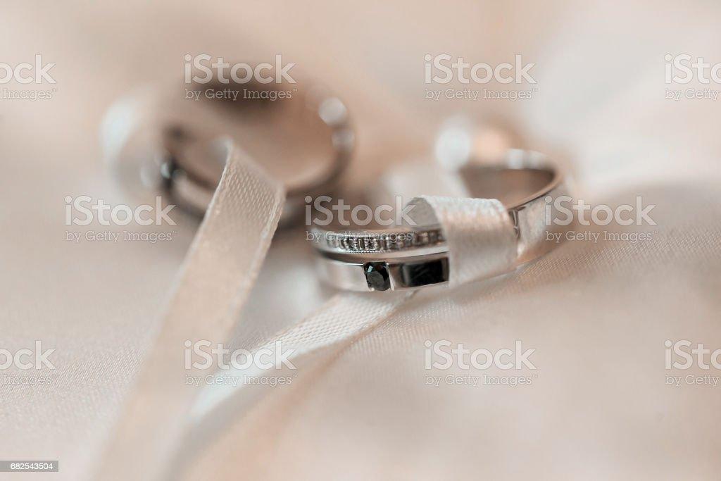 Wedding rings on a white satin pillow. accessories wedding closeup. selective focus stock photo