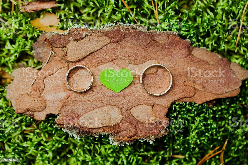 Anillos de boda en un fondo de madera con corazón foto de stock libre de derechos
