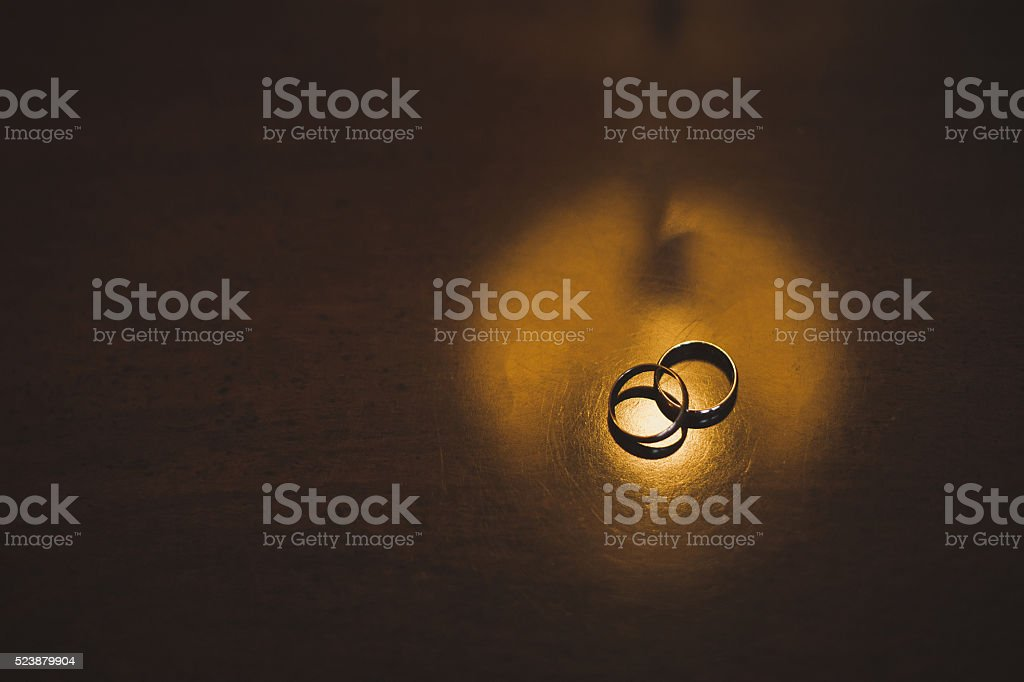 Wedding rings on a wooden table stock photo