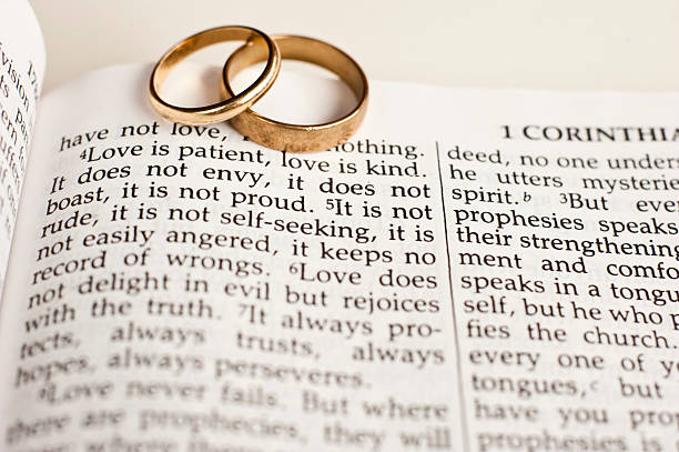 wedding rings on bible passage stock photo