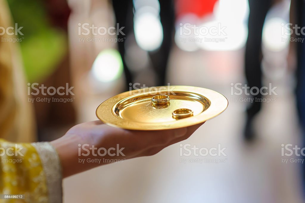 wedding rings on discus at hand of priest stock photo