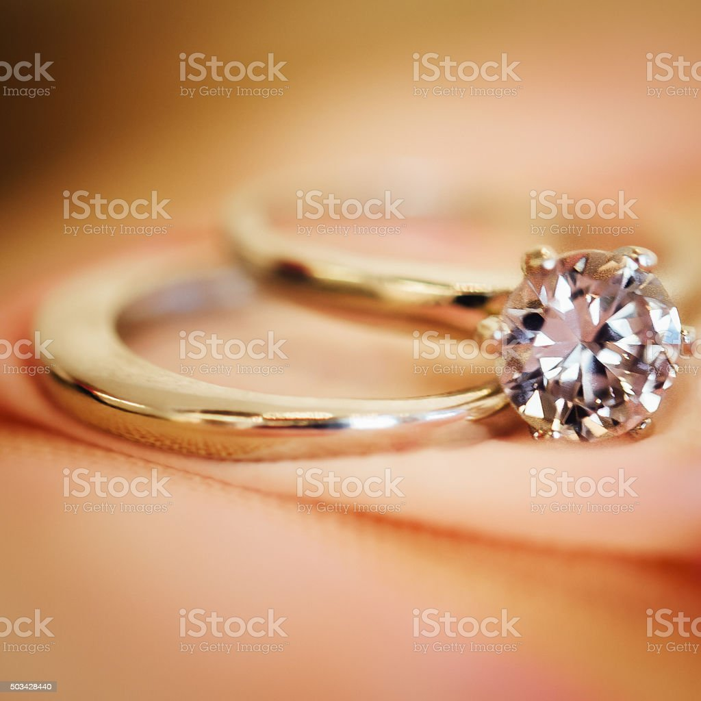 Wedding rings on soft pink background stock photo