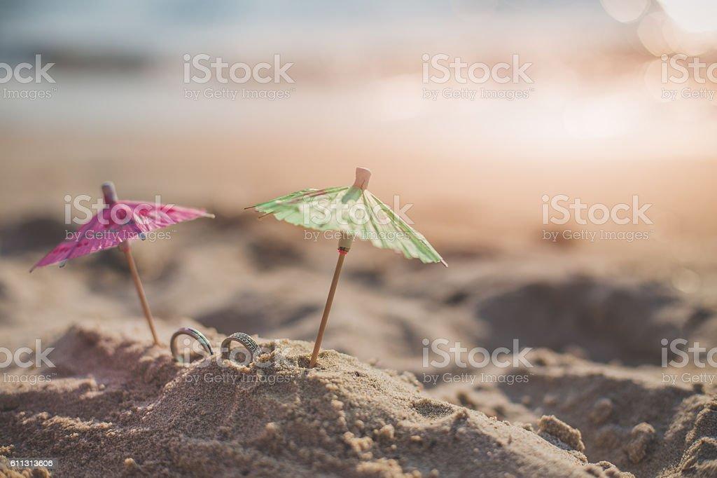 Wedding rings on the beach under drinking umbrella stock photo