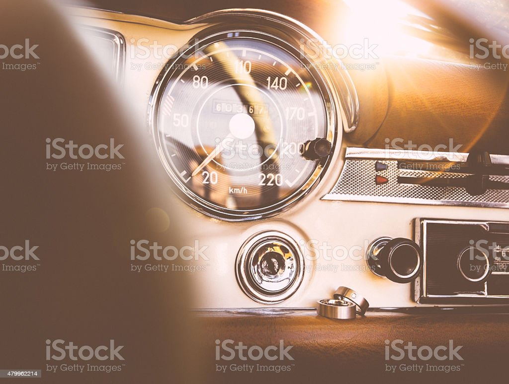 Wedding rings on the dashboard of a vintage car stock photo