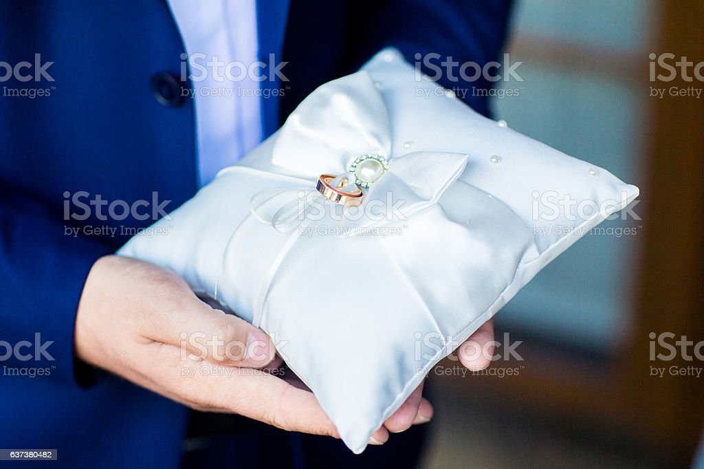 Wedding rings on the lace pillow stock photo