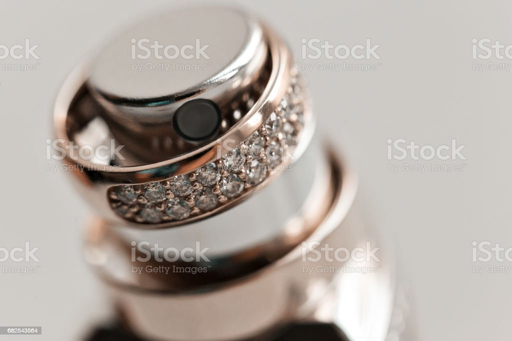 Wedding rings on the perfume bottle. accessories wedding closeup. selective focus stock photo