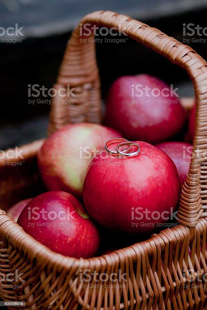 wedding rings on the red apples in basket stock photo