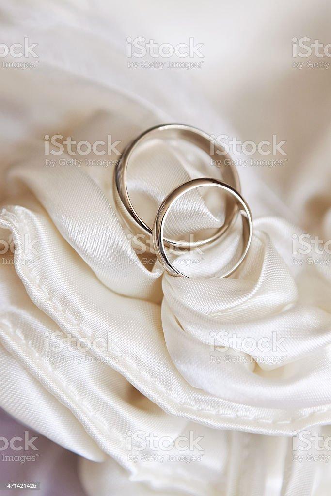 wedding rings on white satin fabric royalty-free stock photo