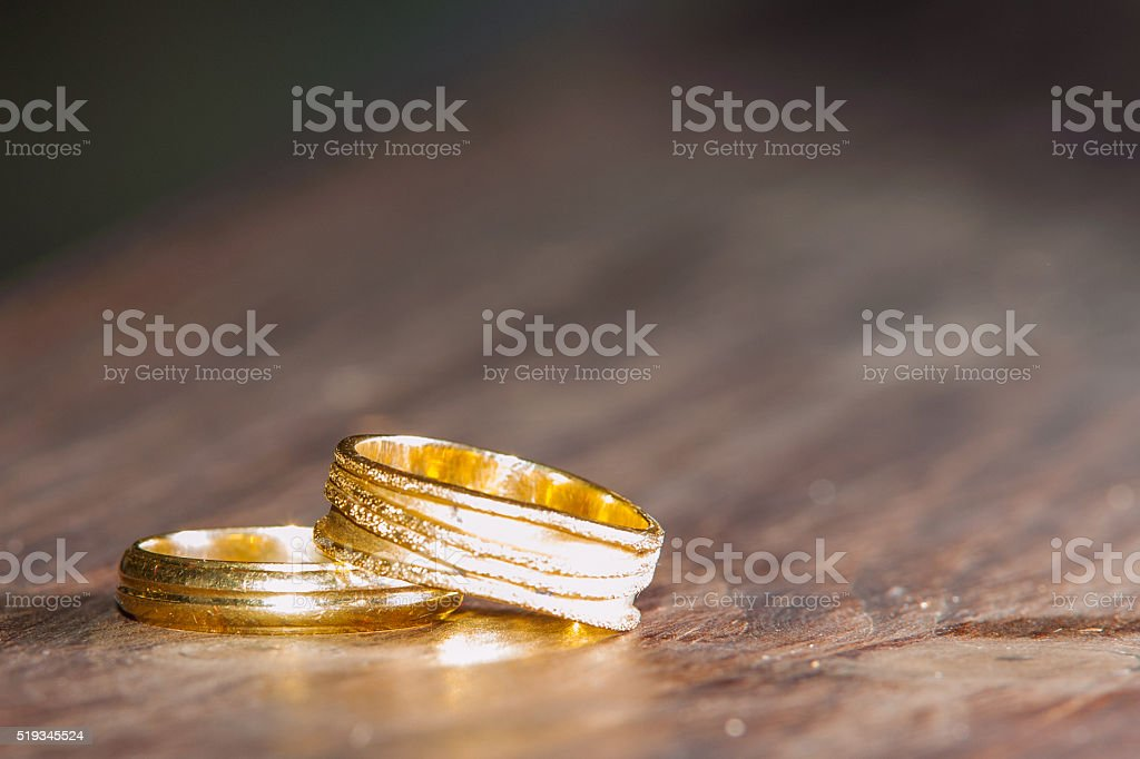 Wedding rings on wood table background stock photo